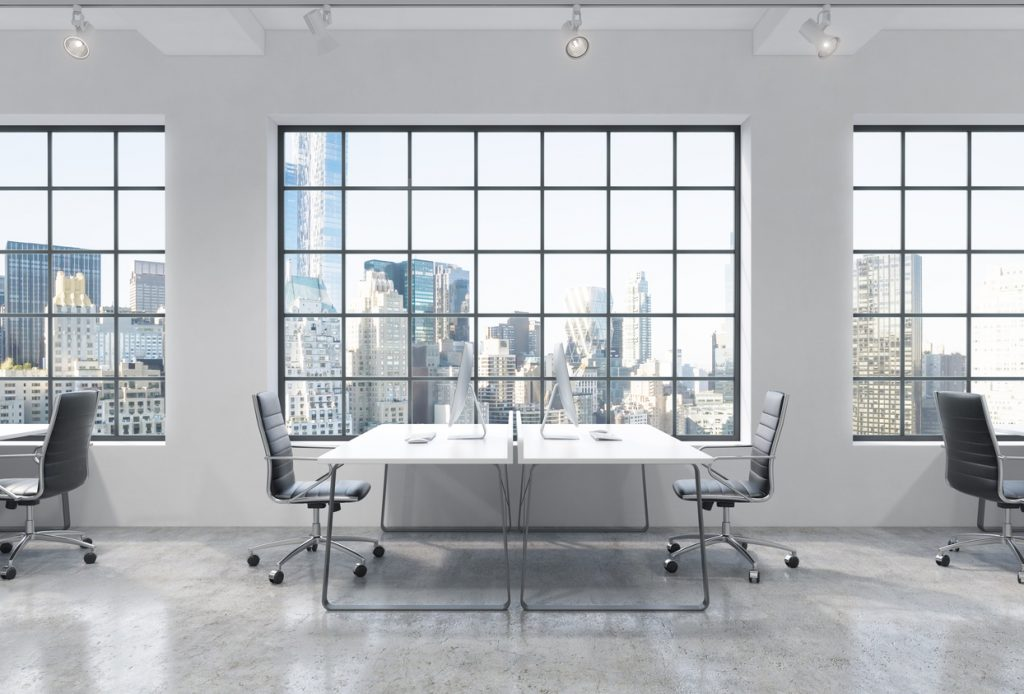 Workplaces in a bright modern loft open space office. Tables are equipped with modern computers. New York panoramic view. A concept of a high quality professional consulting services. 3D rendering.