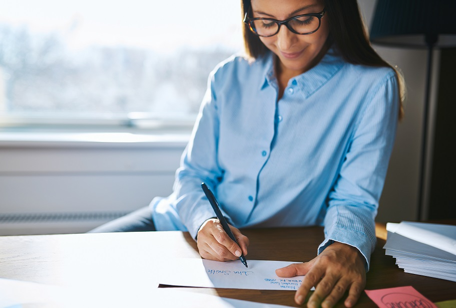 Young woman working from home sitting at her desk in the office writing notes with a smile