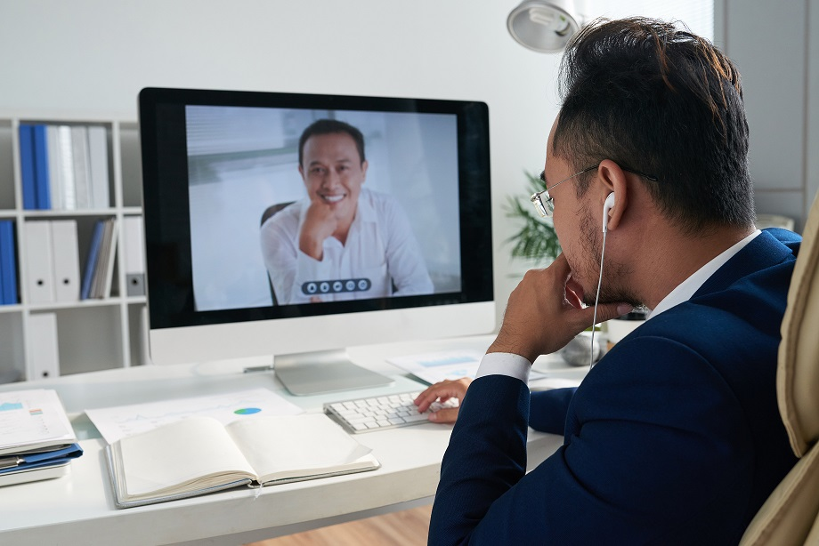 Entrepreneur sitting at his table and videocalling to business partner