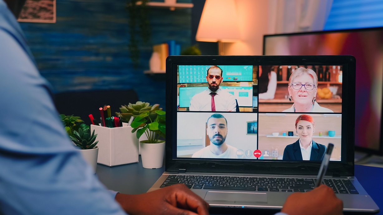 African american employee working remotely discussing with partners online using laptop sitting at desk late at night. Freelancer using modern technology network wireless talking on virtual meeting