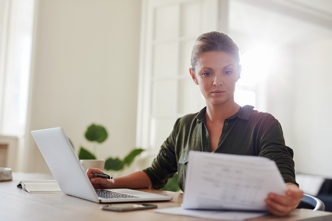 Shot of young woman sitting at table with laptop and reading documents. Beautiful businesswoman working from home office.