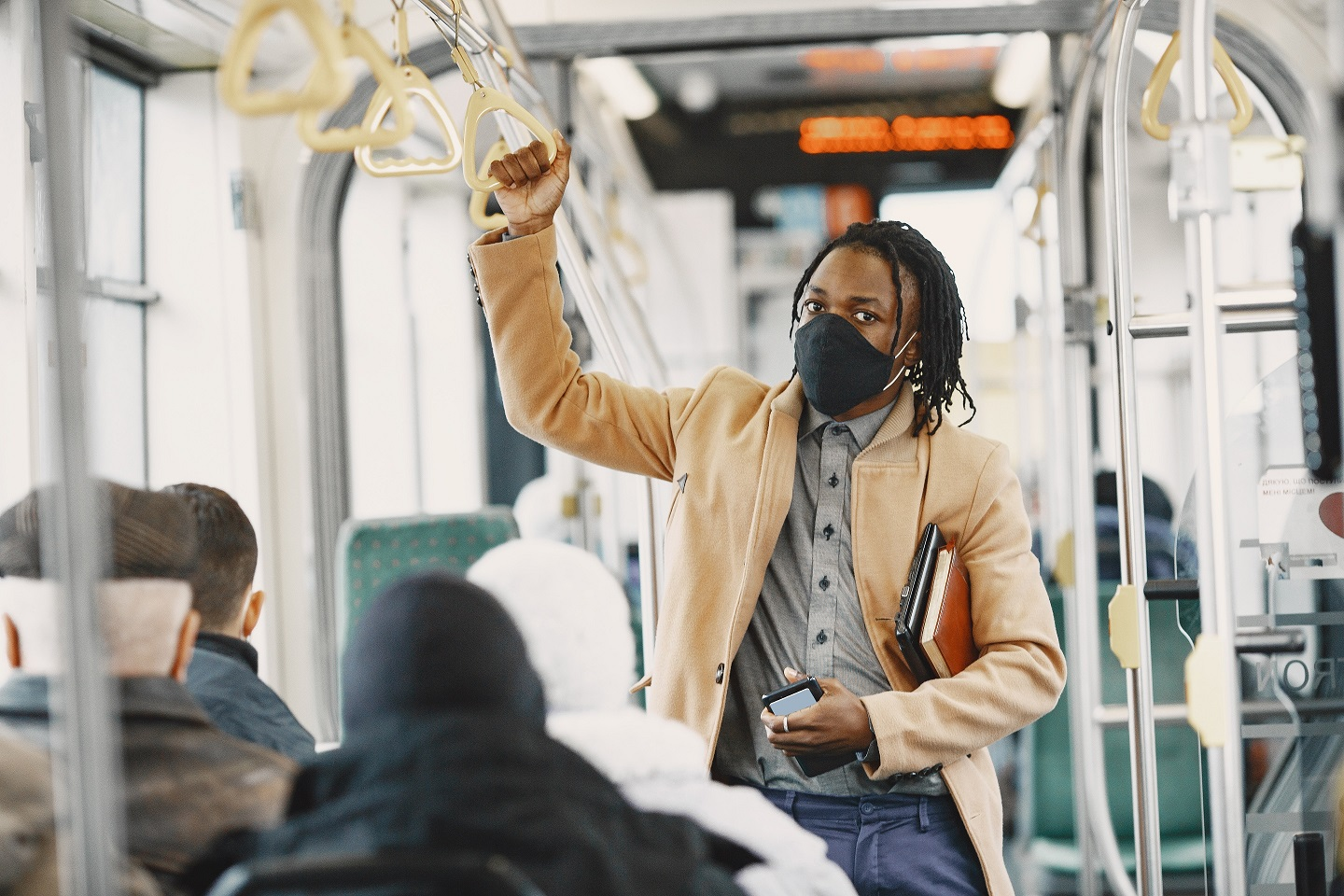African American man riding in the city bus. Guy in a brown coat. Corona virus concept.