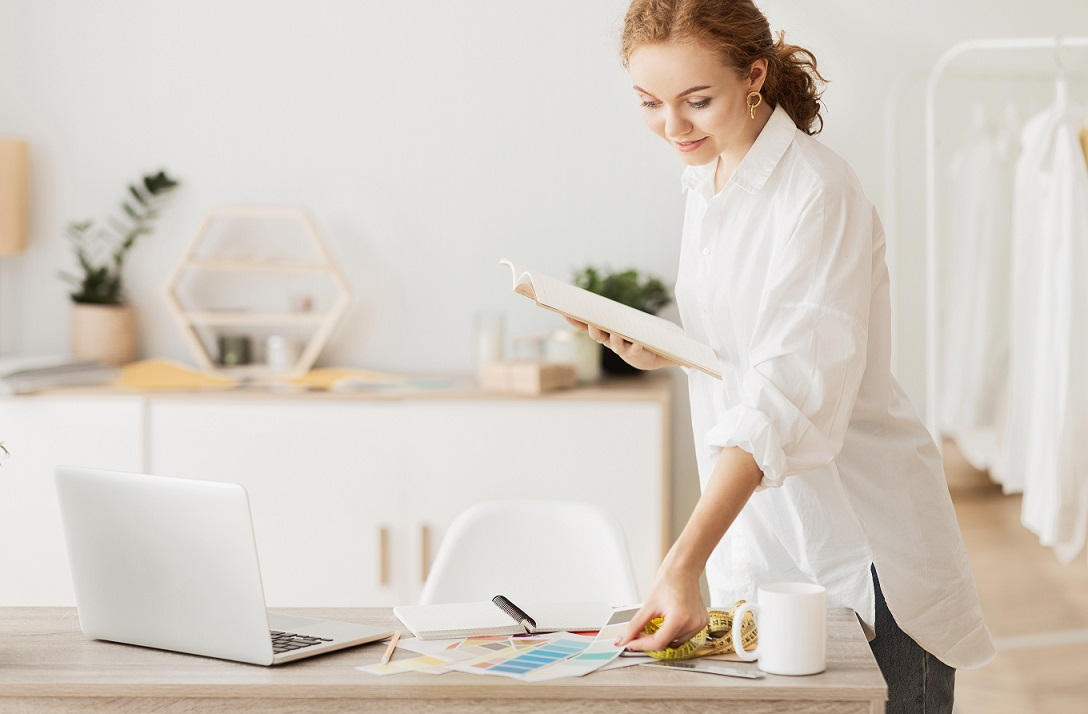 Young fashion designer leaning on office desk, working with laptop and palette in atelier