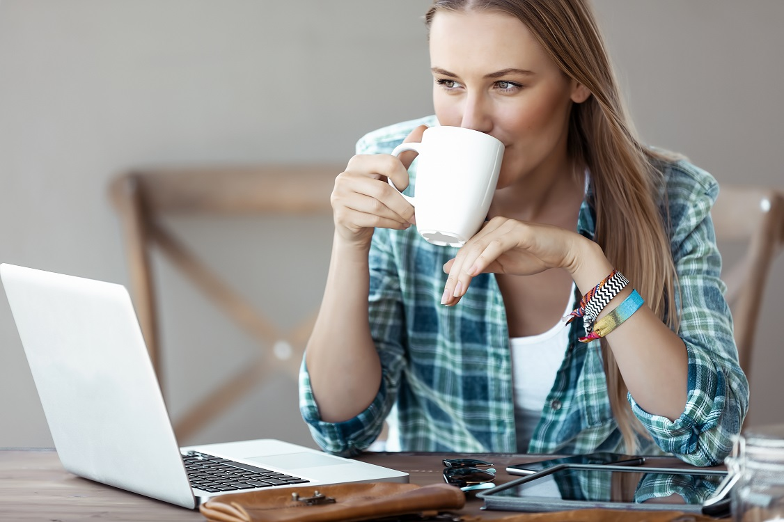 Beautiful Young Woman Working from Home. Pretty Female with Pleasure Drinking Coffee and Working on the Laptop. Freelancing.