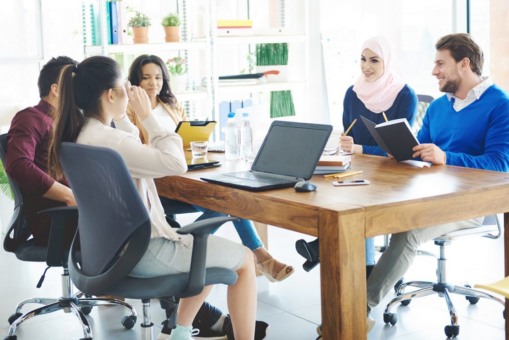 Business people talking in office meeting. Cover magazine visable on the picture and property release including